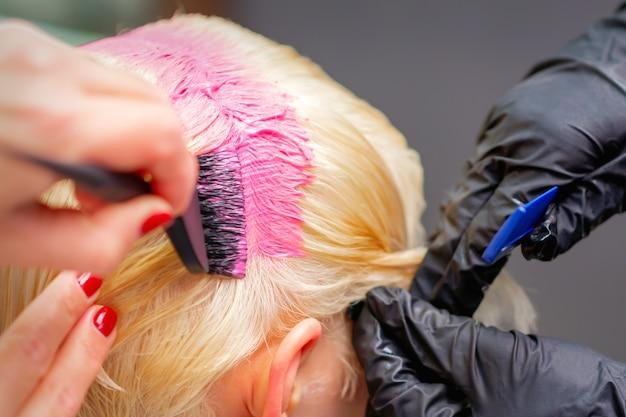 Professionele kapper verft haar van jonge vrouw in roze kleur Premium Foto