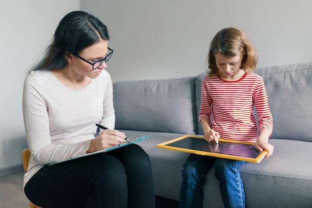 Professionele kinderpsycholoog die met kindmeisje spreekt in bureau Premium Foto