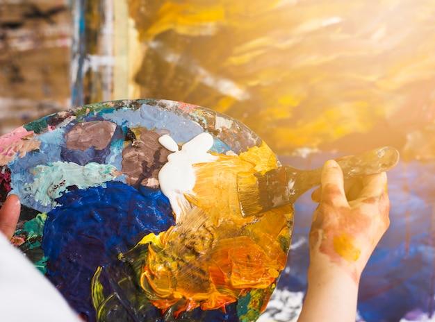 Professionele kunstenaar die olieverf met borstel op palet mengt Gratis Foto