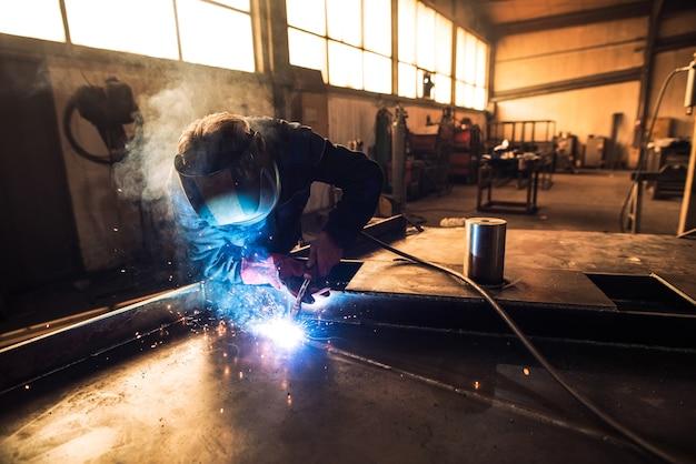 Professionele lasser in beschermende uniform en helm lassen metalen onderdeel in werkplaats Gratis Foto
