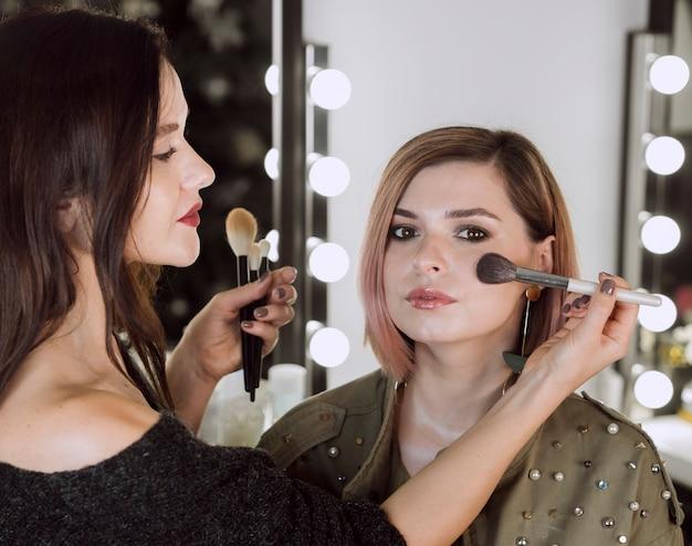 Professionele make-up artist werkmedium shot Gratis Foto