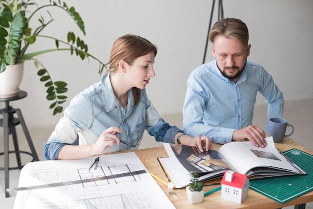 Professionele mannelijke en vrouwelijke architect die catalogus kijken terwijl het werken op kantoor Gratis Foto