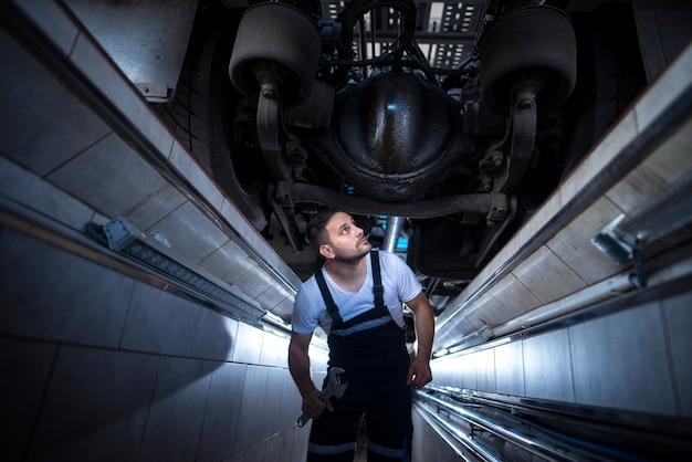 Professionele monteur serviceman onder de vrachtwagen op zoek naar een olielek in de reparatiewerkplaats van het voertuig Gratis Foto