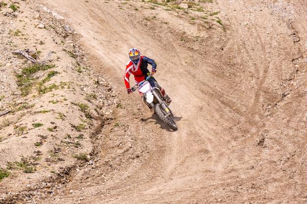 Professionele motorcross motorrijder rijdt over de weg. Premium Foto