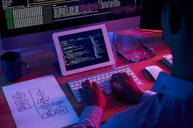 Professionele programmeur werkt laat in het donkere kantoor Gratis Foto