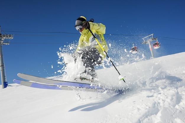 Professionele skiër in gele sportkleding rijden de helling af in georgië, gudauri Premium Foto