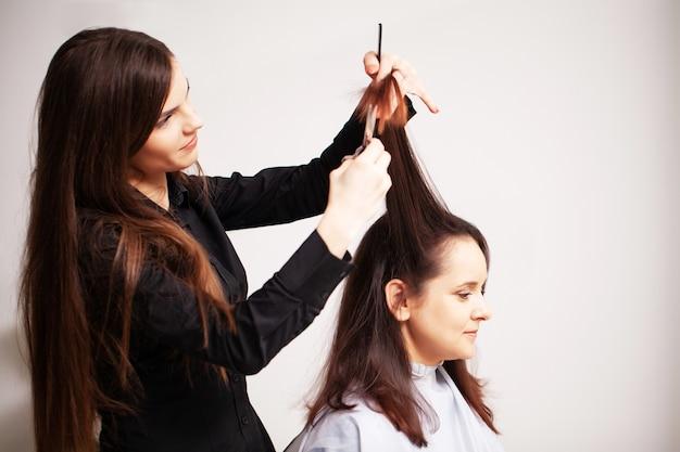 Professionele stylist maakt een jonge vrouw een mooi kapsel. Premium Foto