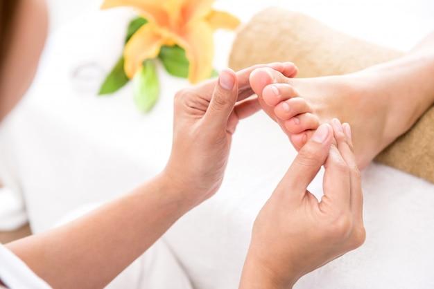 Professionele therapeut die ontspannende reflexology voetmassage geeft aan een vrouw in kuuroord Premium Foto