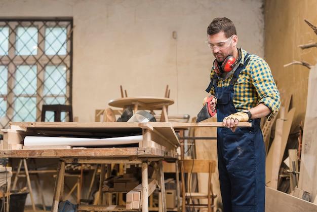 Professionele timmerman die de houten plank met handsaw in de workshop snijdt Gratis Foto
