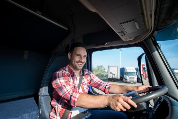 Professionele vrachtwagenchauffeur in vrijetijdskleding die veiligheidsgordel draagt en zijn vrachtwagen naar bestemming rijdt Gratis Foto