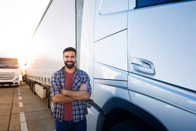 Professionele vrachtwagenchauffeur met gekruiste armen permanent door semi vrachtwagenvoertuig. Premium Foto