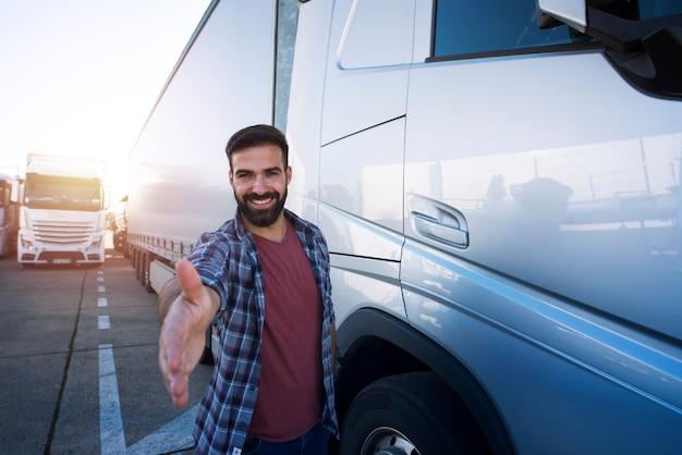 Professionele vrachtwagenchauffeur van middelbare leeftijd die voor zijn vrachtwagen staat en schudt aan nieuwe rekruten. Premium Foto