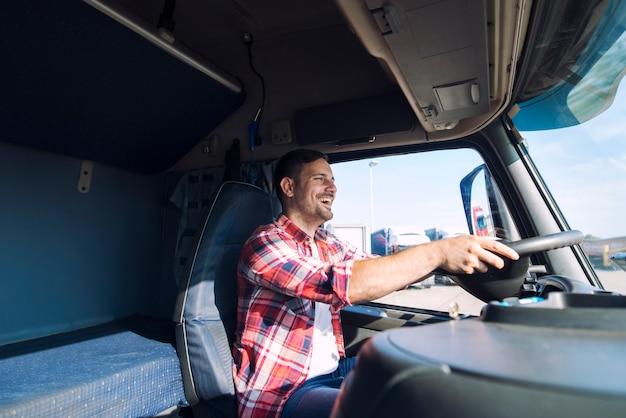 Professionele vrachtwagenchauffeur van middelbare leeftijd in vrijetijdskleding die vrachtwagenvoertuig bestuurt en vracht aflevert op de bestemming Gratis Foto