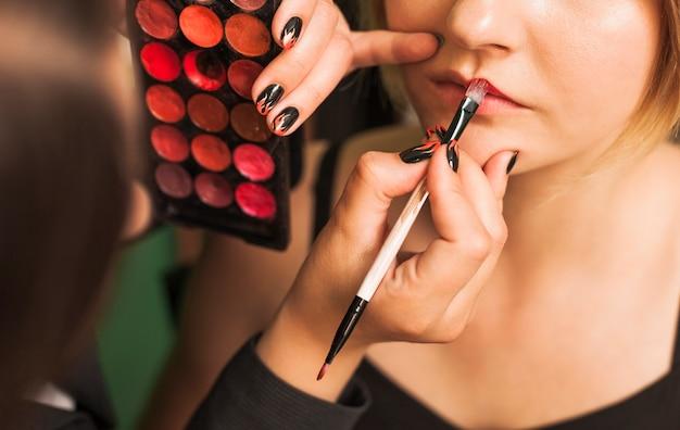 Professionele vrouw die de lippen van het meisje maakt Gratis Foto
