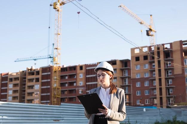 Professionele vrouwelijke architectuur die op klembord bij bouwwerf schrijft Gratis Foto