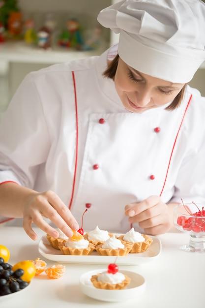 Professionele vrouwelijke banketbakker die mini-fruittaartjes versiert Gratis Foto