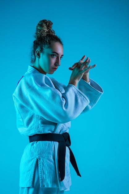 Professionele vrouwelijke judoist in witte judo kimono oefenen en trainen geïsoleerd op blauwe neoned studio achtergrond. Gratis Foto