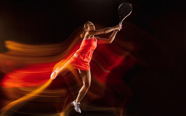 Professionele vrouwelijke tennisspeelster training geïsoleerd op zwarte studio achtergrond in gemengd licht. vrouw in sportpak oefenen. Gratis Foto