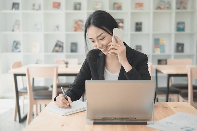 Professionele werkende vrouw die met mobiele telefoon en writngdocument spreekt voor de lijst van informatiegegevens. werken op kantoor met technologie concept. Premium Foto