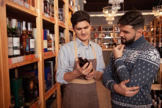 Professionele wijnmaker die zijn mannelijke klant helpt die rode wijn kiest. bebaarde man praten met sommelier bij supermarkt Premium Foto