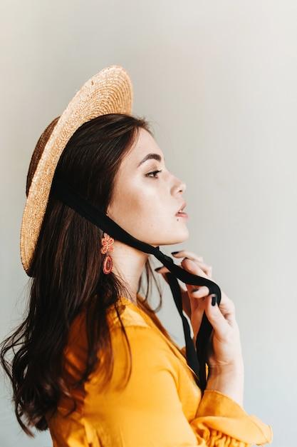 Profiel dat van trots europees meisje met lang haar in oranje hoed is ontsproten. aristocraatvrouw in schipper die op geïsoleerde muur stellen. Gratis Foto