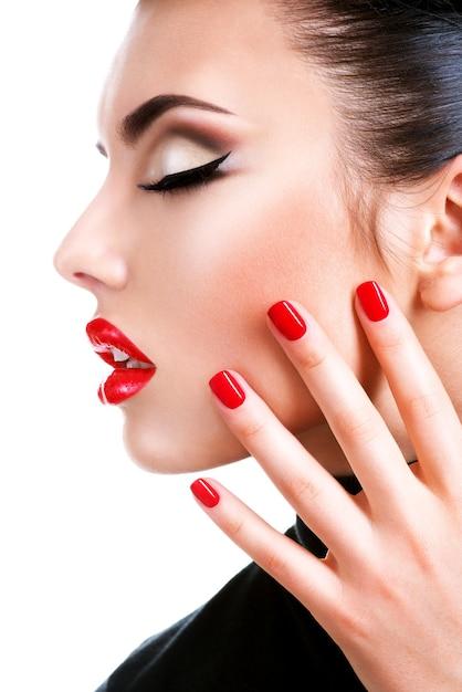 Profiel portret van een mooie jonge vrouw met rode lippenstift. mannequin met heldere glamourmanicure. Gratis Foto