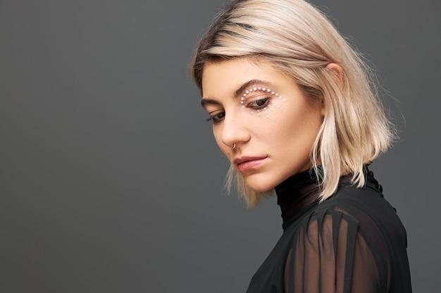 Profiel portret van mooie stijlvolle jonge blonde vrouw in zwarte transparante jurk poseren geïsoleerd neerkijkt met droevige gezichtsuitdrukking, boos gevoel. verlegen ongelukkig schattig meisje naar beneden te kijken Gratis Foto