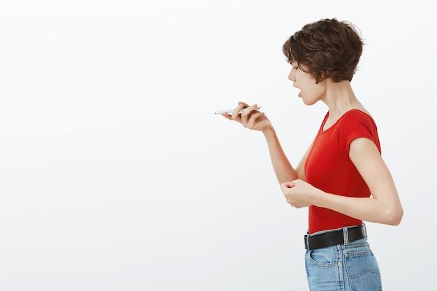 Profiel portret van stijlvolle jongedame met behulp van telefoonrecorder, spraakbericht op smartphone Gratis Foto