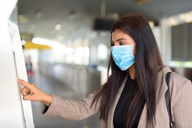 Profiel te bekijken van jonge indiase zakenvrouw met masker kaartje kopen bij skytrain station Premium Foto