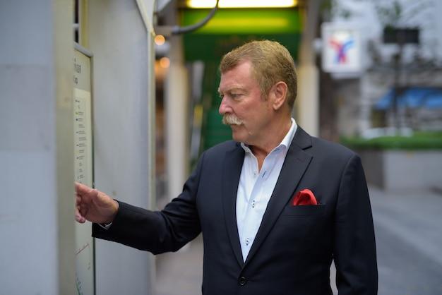 Profiel te bekijken van knappe senior zakenman met snor de kaart in de stad controleren Premium Foto