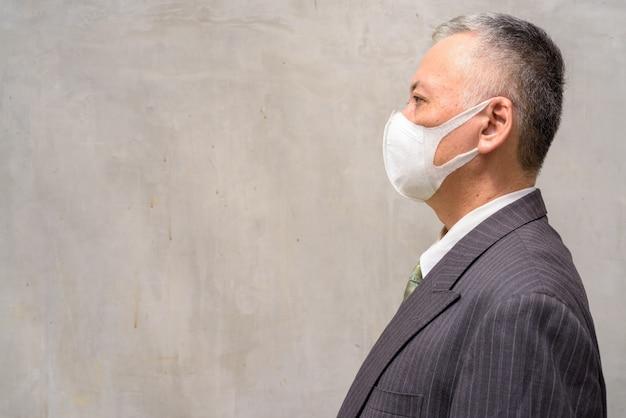 Profiel te bekijken van volwassen japanse zakenman met masker buitenshuis Premium Foto