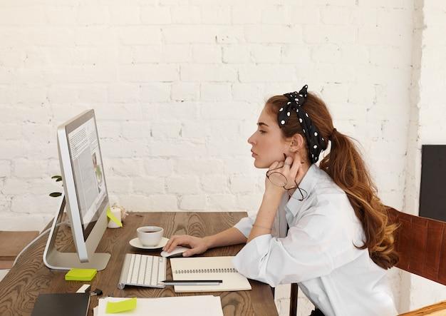 Profiel van :: aantrekkelijke geconcentreerde jonge europese vrouwelijke blogger of columnist zit op haar werkplek achter desktopcomputer, bezig met nieuw materiaal voor haar blog, mok en briefpapier op bureau Gratis Foto