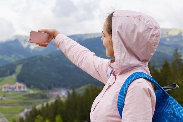 Profiel van actieve reiziger die foto op bergachtergrond neemt, video voor reisblog opneemt, tijd met plezier doorbrengt op vakantie, alleen wandelt, warme kleren draagt. Premium Foto