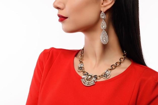 Profiel van een mooie vrouw in rode avondjurk met ketting en oorbellen Premium Foto
