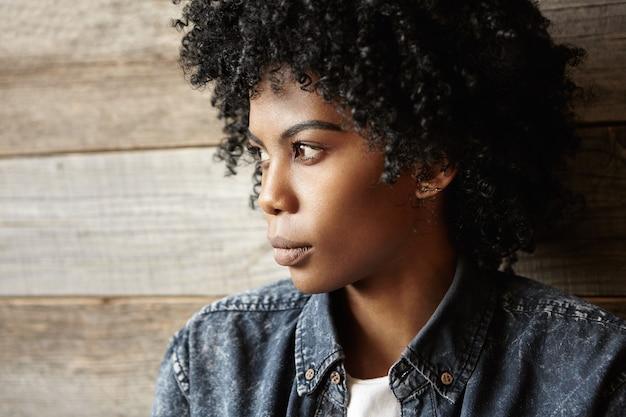 Profiel van :: modieus afrikaans meisje close-up met afro kapsel stijlvolle denim shirt dragen Gratis Foto