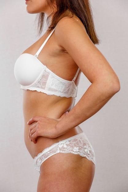 Profiel van mooi slank die vrouwenlichaam op grijs wordt geïsoleerd Premium Foto