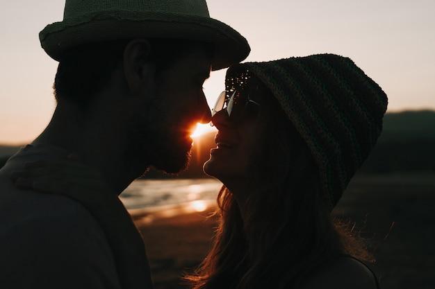 Profielen van romantisch paar die elkaar op achtergrond van zonsondergangstrand bekijken. Gratis Foto