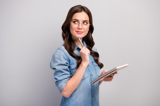 Profielfoto van mooie freelancer dame houd persoonlijke planner minded slimme creatieve persoon pen op kin slijtage specs casual jeans denim overhemd geïsoleerde grijze kleur Premium Foto