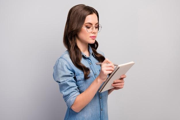 Profielfoto van mooie zakelijke dame houd persoonlijke planner nota baas informatie slijtage specs casual jeans denim overhemd geïsoleerde grijze kleur Premium Foto
