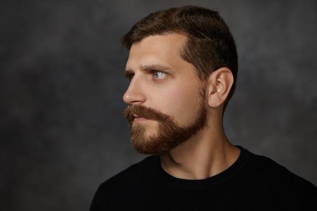 Profielportret van aantrekkelijke macho man met nette getrimde baard en snor poseren geïsoleerd op blinde muur, fronsen, wantrouwen uiten, wegkijken, met een strikte ernstige uitdrukking Gratis Foto