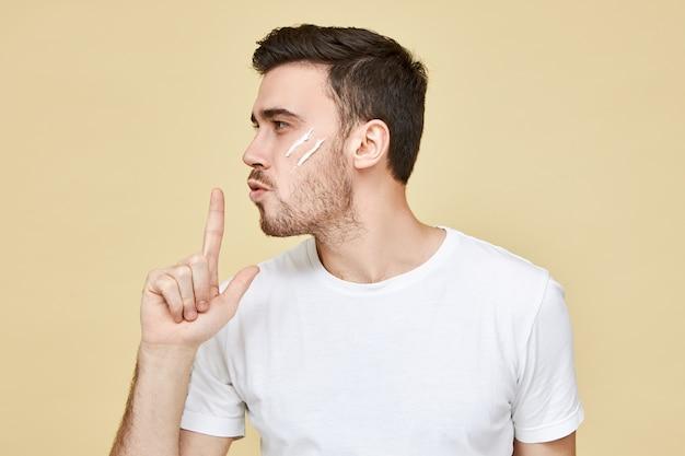 Profielportret van aantrekkelijke macho man met stoppels en zwart haar poseren met de hand op zijn lippen en blazen op de wijsvinger alsof hij psitol gebruikt, met zelfverzekerde gezichtsuitdrukking Gratis Foto