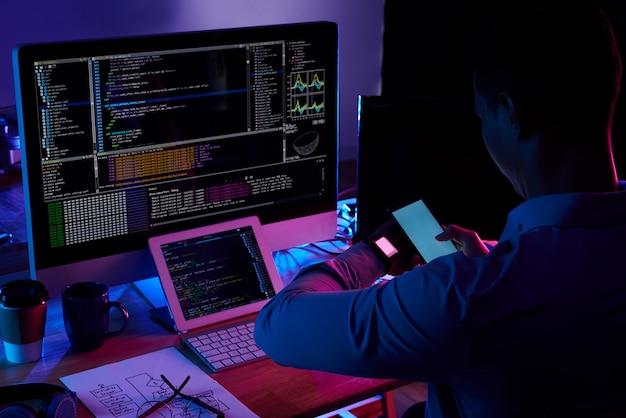 Programmeur scannen scherm op zijn smartwatch met smartphone camera Gratis Foto