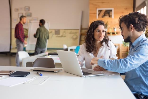Projectpartners die ideeën bespreken en samen laptop gebruiken Gratis Foto