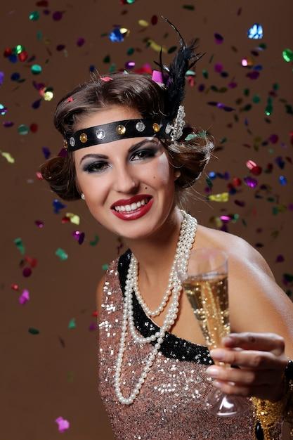 Proost, feestvrouw met confetti achtergrond Gratis Foto