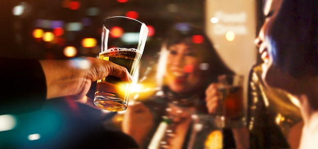 Proost van het rammelen van vrienden met bier drinken in feestavond na het werk Premium Foto
