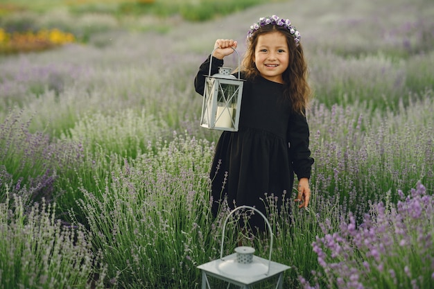Provence kind ontspannen in lavendel veld. kleine dame in een zwarte jurk. meisje met tas. Gratis Foto
