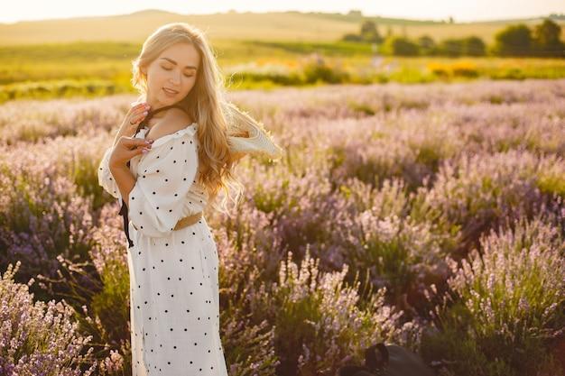 Provence vrouw ontspannen in lavendel veld. dame in een witte jurk. meisje met een strohoed. Gratis Foto