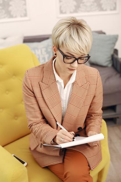 Psycholoog die met glazen op een stoel op het kantoor zit Gratis Foto