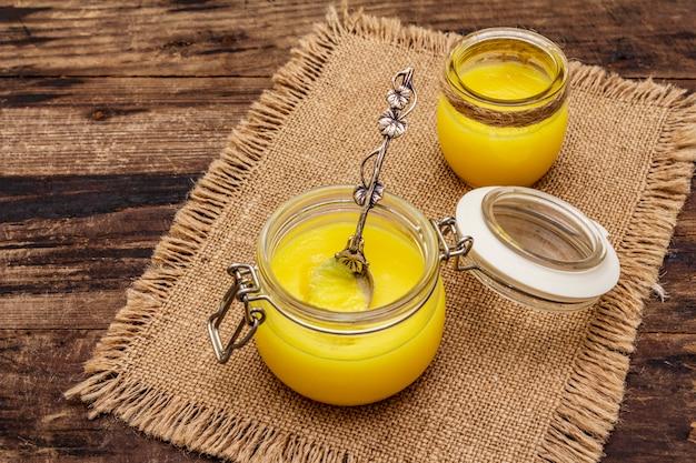 Pure of desi ghee (ghi), geklaarde gesmolten boter. gezonde vetten kogelvrij dieetconcept of paleostijlplan. glazen pot, zilveren lepel op vintage zak. Premium Foto