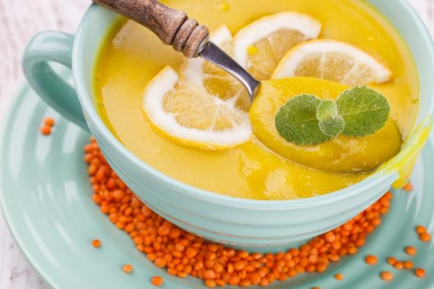 Pureer soep met rode linzen, met mint en citroenwiggen Premium Foto